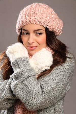 Girl in warm winter woollies looking away smiles photo