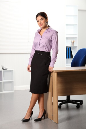 Beautiful business woman standing near office desk photo