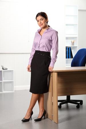 blusa: Mujer de negocios hermosa permanente cerca de escritorio