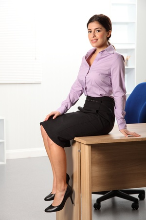 Young business woman sitting on office desk photo