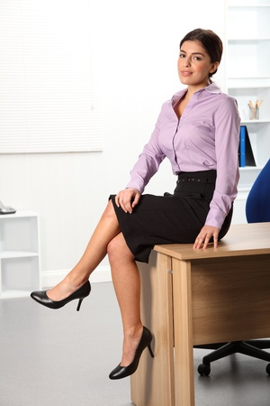 Beautiful young businesswoman sitting on office desk photo