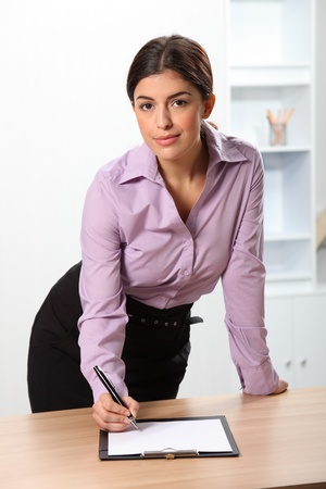 Beautiful confident business woman writing at desk photo