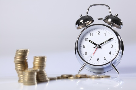 Time is money concept. Gold pound coins in foreground blurred, with a traditional silver and chrome alarm clock in background in sharp focus. photo