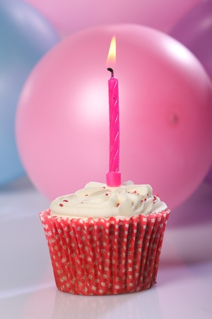 Cream cup cake with single pink candle, indicating celebration for a girl. Pink, blue and purple balloons in background. Stock Photo - 9613723