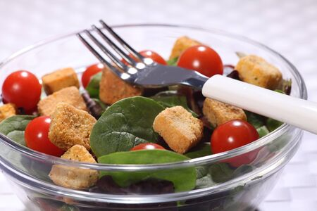 includes: Healthy green salad in a glass bowl, set on a weaved place mat. Salad includes cherry tomatoes and croutons. Fork placed on top of the salad.