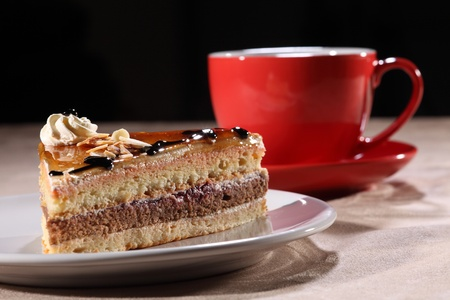 layer cake: Tasty slice of layered coffee cake on a white plate, along with red coffee cup and saucer. Cake topped with syrup, chocolate sauce, whipped cream and flaked nuts.