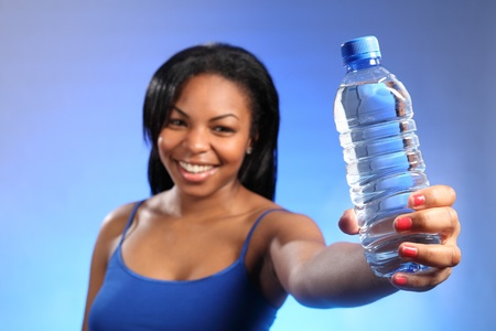 out of water: Health and wellbeing shot of beautiful black woman, with a big, happy smile, holding out a bottle of water to the camera. Focus is sharp on the water with woman blurred in background.