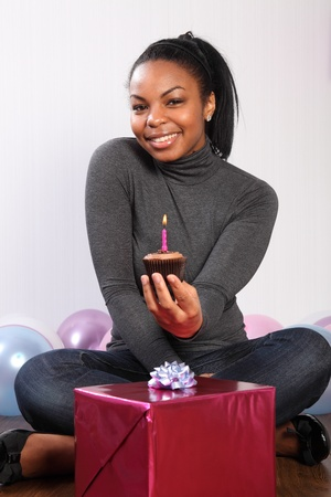 Birthday party. Time to celebrate for beautiful, smiling young black woman, sitting on the floor at home, with a birthday present, surrounded by balloons and holding a chocolate cup cake. photo