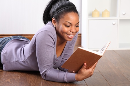 Beautiful young black girl, big smile, wearing jeans and purple top, lying on the floor at home, reading a book. photo
