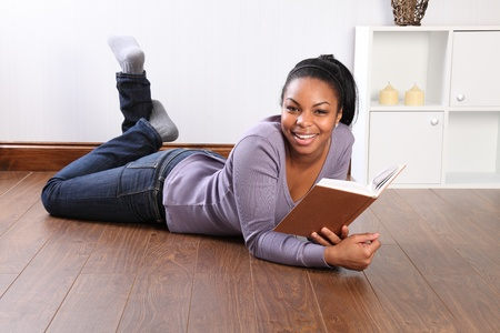 Beautiful young black student girl, big smile, wearing jeans and purple top, lying on the floor at home, reading a book. photo