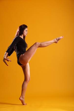 Girl in dance pose right leg extended arms back photo