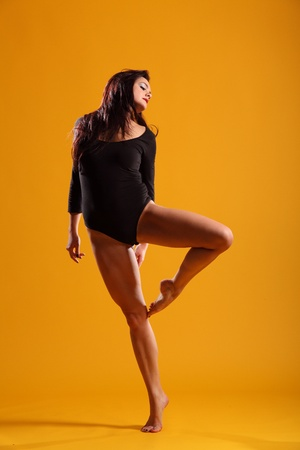 Girl leg bent in dancing pose on yellow background