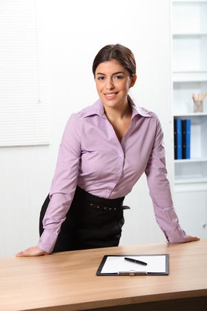 Smiling business woman standing behind office desk photo
