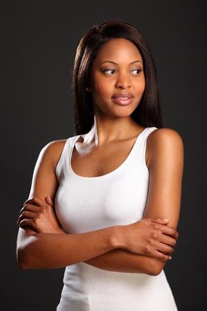Hermosa mujer negra con armas dobladas en chaleco blanco Foto de archivo