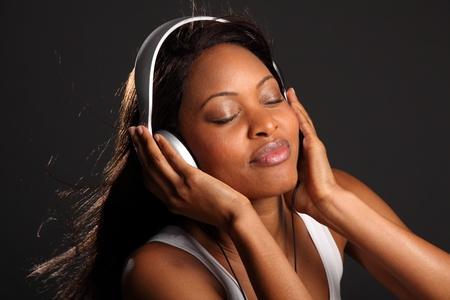 escuchando musica: Impresionantes ojos felices mujer negra cerraron escuchar música