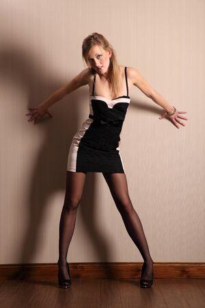 Long legged model strikes sexy pose in short dress photo