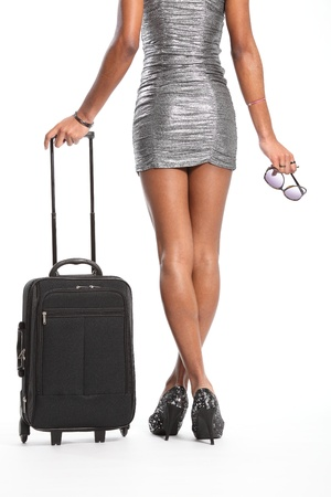 silver dress: Sexy long legs of woman waiting with suitcase