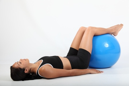 knees bent: Athletic woman knees bent working on exercise ball Stock Photo