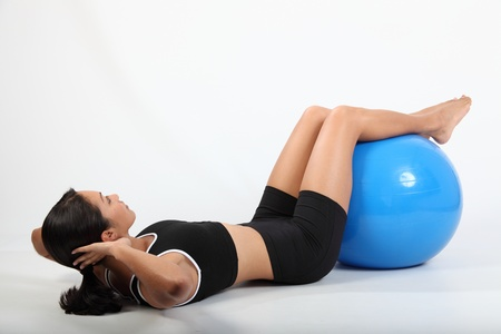 knees bent: Athletic woman knees bent doing crunches on exercise ball
