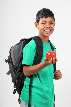 Smiling young school boy holding red apple photo
