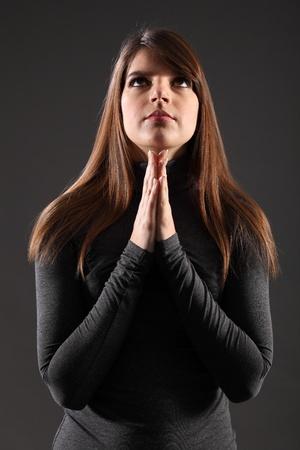 long sleeve: Beautiful young caucasian, woman with long hair, praying.