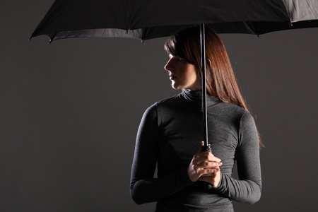 emphasise: Beautiful young woman standing under the protection and cover of an umbrella. Model wearing dark clothing, head turned on profile. Dramatic lighting to emphasise danger and need for shelter.