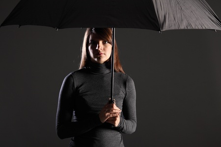 emphasise: Beautiful young woman standing under the protection and cover of an umbrella. Model wearing dark clothing, looking straight into camera. Dramatic lighting to emphasise danger and need for shelter. Stock Photo