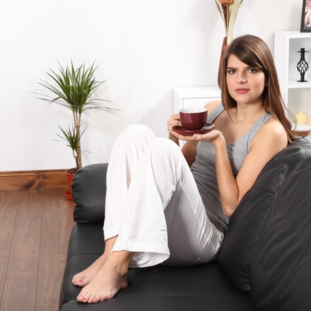 Beautiful young, caucasian woman, sitting on the sofa at home drinking coffee. She is wearing white linen trousers and a grey vest. photo