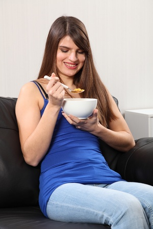 Beautiful young, caucasian woman, sitting on the sofa eating breakfast cereal. She is wearing blue jeans and vest. photo