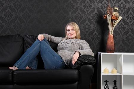 fille pull: Belle jeune femme blonde assise sur le canap� de cuir noir � la maison, portant un chandail en tricot gris, blue jeans et relaxant juste. Banque d'images