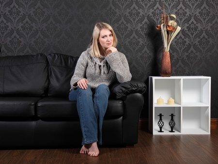 Beautiful young blonde woman sitting on black leather sofa at home, wearing casual grey knitted sweater, blue jeans and just relaxing. photo