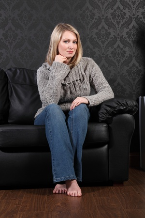 Thoughtful moment for beautiful young blonde woman sitting on black leather sofa at home, wearing casual grey knitted sweater, blue jeans and just relaxing. photo