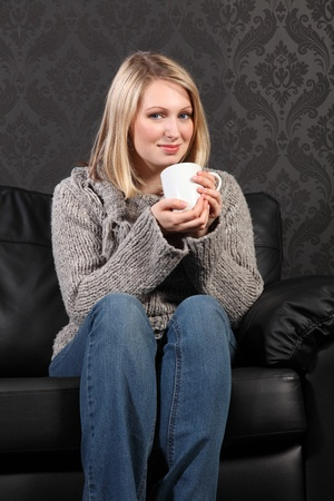 Thoughtful moment for beautiful young blonde woman sitting on black leather sofa at home drinking coffee, wearing casual grey knitted sweater, blue jeans and just relaxing. photo