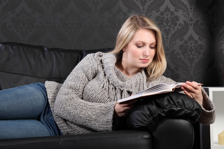 Quiet time for beautiful young blonde woman sitting reading a book on black leather sofa at home, wearing casual grey knitted sweater, blue jeans and just relaxing. photo