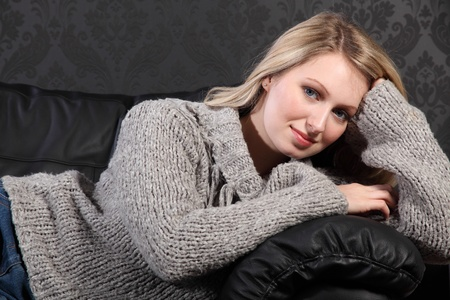 Beautiful young blonde woman lying across black leather sofa at home, wearing casual grey knitted sweater. photo