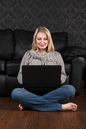Happy beautiful young blonde girl sitting on the floor at home, bare foot wearing blue jeans and knitted top, surfing the internet and facebook with her laptop computer. photo