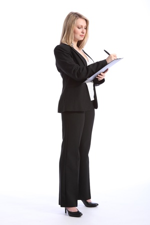 trousers: Full body shot of a beautiful blonde business woman writing and taking notes on a clipboard. She is wearing a smart black business suit and high heels.
