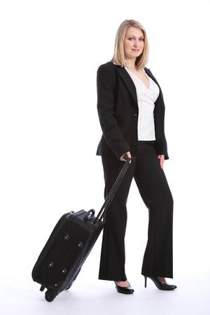 Full length of a beautiful blonde business woman wearing a smart black business suit, walking with a suitcase. photo