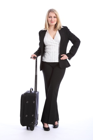 Beautiful young blonde business woman wearing a smart black business suit, standing in a relaxed pose waiting with a suitcase. photo