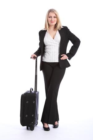 alumnos en clase: Hermosa joven rubia mujer de negocios llevaba un traje de negocios negro inteligente, en una pose relajada esperando con una maleta.
