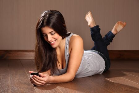 young girl feet: Beautiful happy woman relaxed reading text message