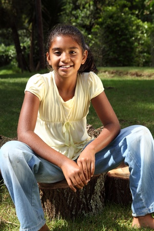 Young happy school girl outdoors sitting on logs in sunshine photo