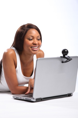 african american woman smiling: Black woman lying on floor using laptop and webcam Stock Photo