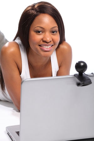 Black woman lying on floor keeping in touch with friends on laptop and webcam photo