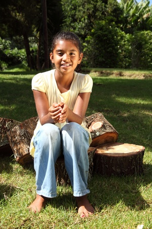 Young happy school girl outdoors sitting on logs bare footed photo
