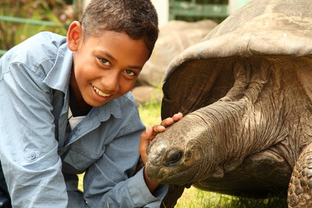 Boy visits Jonathan the tortoise on St Helena. Jonathan the famous giant tortoise who is estimated to be 150 to 200 years old weighing 440 pounds photo