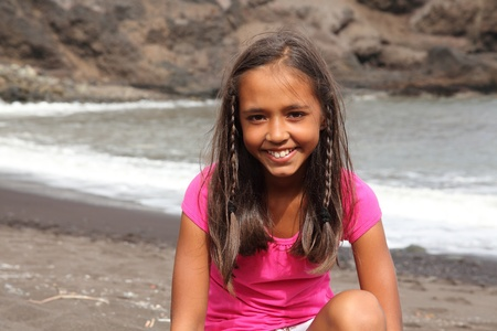 Cute smile from young school girl sitting on the beach