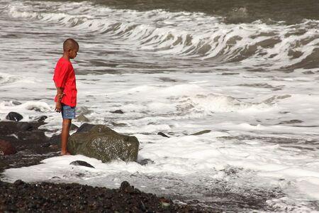 Ethnic school boy on beach watching the surf photo