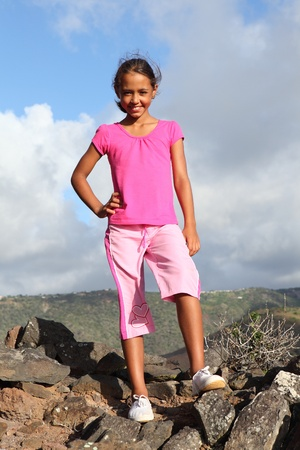 Young girl standing on the mountain summit