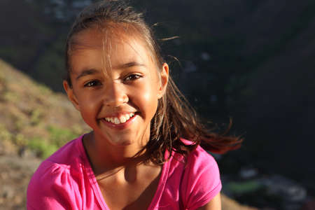 School girl beautiful smile in late afternoon light on windy day photo